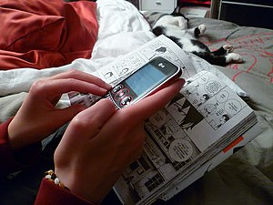 English: French teenage girl texting while rea...