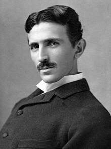 head-and-shoulder shot of slender man with dark hair and moustache, dark suit and white-collar shirt