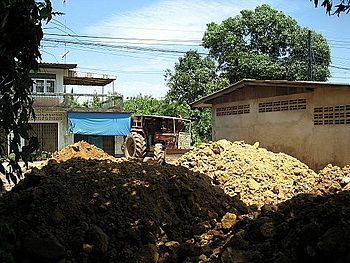 English: A bulldozer levels dirt fill on a Tha...