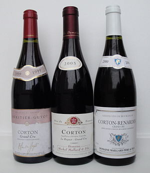 "Lieu-dit - Three bottles of red Corton AOC wine, from the same appellation, showing different usages of lieu-dit (climat) designations on labels, in addition to the appellation's name. On the left, a wine with no indication of specific lieu-dit, in the middle a wine where Le Rognet is indicated in small print, and on the right a wine from Les Renardes, written hyphenated with Corton as ""Corton-Renardes""."