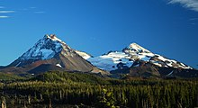 Two volcanoes rise above a landscape of mixed forest and lava, with a glacier spanning the area between the two peaks