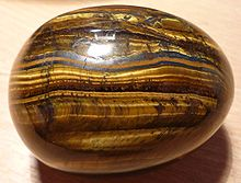 """Photograph of a polished ovoid stone with bands containing shimmering golden fibers"""