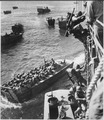 U.S. troops go over the side of a Coast Guard manned combat transport to enter the landing barges at Empress Augusta... - NARA - 513194.tif