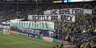 Fans in a stadium display two large banners which read 'The Boys From Seattle Are Back' with artwork of soccer players in green and blue uniforms.