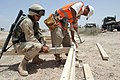 US Navy 040519-M-8049T-199 A Seabee assigned to Naval Mobile Construction Battalion Seven Four (NMCB-74) supervises a local Iraqi worker as he nails in a beam.jpg