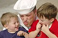 US Navy 050731-N-5362A-198 Photographer's Mate 2nd Class Dennis Timms makes a funny face to amuse his two sons, after greeting his family at pier 14 on board Naval Station Norfolk.jpg