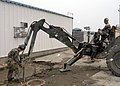 US Navy 070302-N-6247M-020 Construction Electrician Constructionman Joshua Gonzales, from San Diego, Calif., attaches old wires outside a prefabricated building while Equipment Operator Constructionman Jonathan Rust, from Tular.jpg
