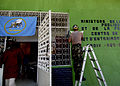 US Navy 070906-N-6278K-008 Builder 1st Class Manuel Gradillas, a Seabee assigned to Construction Battalion Maintenance Unit (CBMU) 202, paints a medical symbol on the wall of a local health training center.jpg