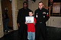 US Navy 071206-N-6700F-036 Yeoman 1st Class Keith Sowell and Engineman 1st Class Alonzo Cordon recognize the Norview Elementary 5th grade Student of the Month by presenting him with a certificate from Norfolk Naval Brig Comman.jpg