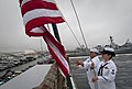 US Navy 100610-N-5319A-031 Hospital Corpsman 2nd Class Mary Schlunsen, right, and Information Systems Technician 3rd Class Vincente Viloria raise the national ensign during morning colors aboard USS New Orleans (LPD 18).jpg