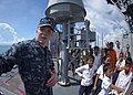 US Navy 100611-N-6770T-174 Operations Specialist 3rd Class Essig explains the ship's defensive weapons to visiting Cambodian orphans.jpg