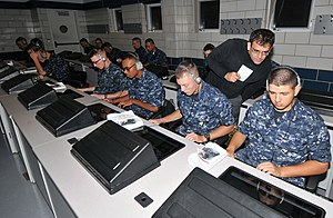 BBN Technologies - Dr. Talib Hussain, senior scientist at BBN Technologies, looks over the shoulder of a recruit during a training session on the Virtual Environments for Ship and Shore Experiential Learning system at Recruit Training Command.