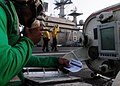 US Navy 110605-N-SB672-050 Aviation Boatswain's Mate (Equipment) Airman Aaron Jones uses the sound-powered telephone in the center-deck hatch to re.jpg