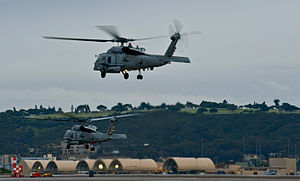 US Navy 111213-N-HW704-001 Two MH60R Sea Hawk helicopters assigned to the Saberhawks of Helicopter Maritime Strike Squadron (HSM) 77 take off from.jpg