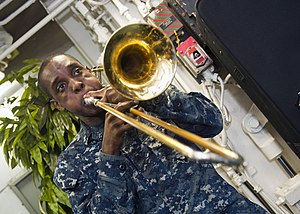 US Navy 120123-N-FI736-185 A Sailor plays trombone during a Dr. Martin Luther King, Jr. birthday celebration aboard the aircraft carrier USS Enterp.jpg