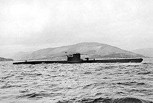 A side view of a surfaced submarine, seen in the middle distance; she is sailing in coastal waters and a mountainous landscape is in the background.