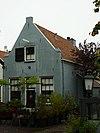 foto van Hoekhuis met zadeldak tussen puntgevels met pothuis