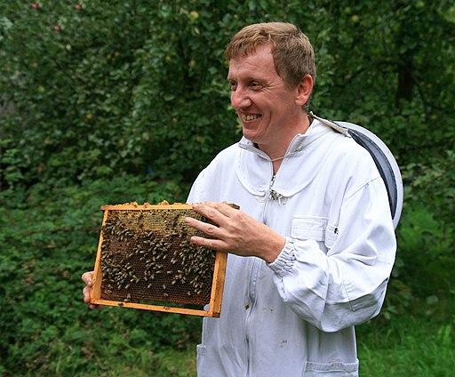Beginnend imker krijgt uitleg nieuw imkerpak voorlichting bijen op raam bijenkast