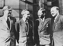 Vier mannen in pak, elk met een medaille op de linkerborst