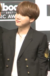 Suga, in a black suit, holds his hands behind his back, looking left