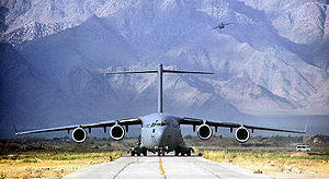 437th Operations Group - A C-17 Globemaster III from Charleston Air Force Base, S.C., moves up the taxiway as another begins its climb over the mountains surrounding Bagram Air Base, Afghanistan