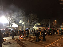 People mill about a fire and larger gatherings at night on a wintry street by a police building