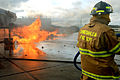 A U.S. Air Force firefighter prepares to extinguish flames during a training exercise on a concrete pad known as a burn pad at Spangdahlem Air Base, Germany, Jan. 8, 2014 140108-F-OP138-114.jpg