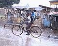 A boy riding a bicycle through the rains.jpg