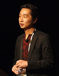 Photo of a Japanese man in a black jacket in front of a black background.