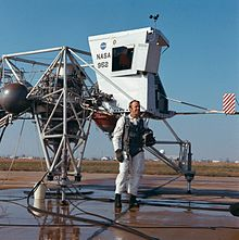 Shepard stands in a white flight suit in front of a vehicle made of tubing, with two metal spheres and a small cabin
