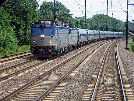 An electric Amtrak train with two AEM-7 locomotives running through New Jersey on the Northeast Corridor Amtrak Regional viewed from NJ Transit train.jpg