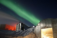 A low shot of a station at the South Pole taken at night. Nearest the front of the photo is a metal structure with a curved roof and a large, open door from which bright light emanates. Slightly further in the distance are two larger buildings. The sky above is a dark blue littered with stars and a green light present across the middle of the sky.