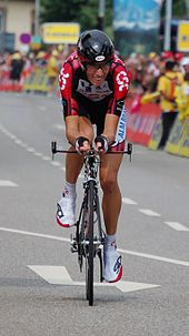 A cyclist on his bicycle, wearing a red and black jersey with white trim.