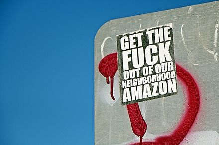 A sticker expressing an anti-Amazon message is pictured on the back of a street sign in Seattle. Anti-Amazon sticker.jpg