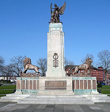 A column flanked by two lions and surmounted by a statue of Peace and a soldier. There are bronze plaques on the base of the monument.