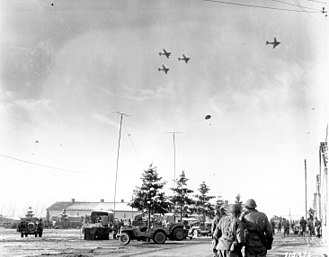 Siege of Bastogne - 101st Airborne Division troops watch as C-47s drop supplies over Bastogne, 26 December 1944