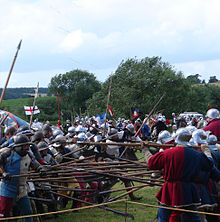 Men in armour poke their polearms at each other, while arrows fly overhead.