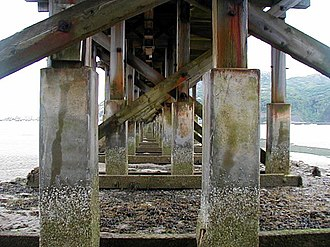 Barmouth Bridge - Underside view of the bridge and its piers. Note the concrete reinforcement towards the base of the wooden piers