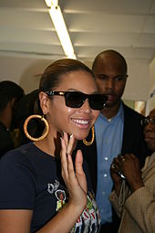 A woman wearing a printed t-shirt, sunglasses and hoop earrings. She is smiling and waving, and various people are in the background.
