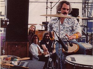 Bill Kreutzmann - Bill Kreutzmann, playing a djembe. Grateful Dead band members Brent Mydland, Bob Weir and Jerry Garcia (from left to right) are in the background. Denver, Co.