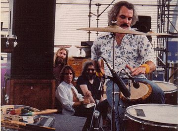 Grateful Dead members in the early 1980s: Brent Mydland, Bob Weir, and Jerry Garcia watch Bill Kreutzmann play the drums. Not pictured are Phil Lesh and Mickey Hart. Billbongo.jpg