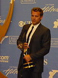 A man with dark hair, wearing a black suit, including a black tie and white T-shirt also holding a gold statuette.