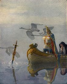 "Illustration from ""The Boy's King Arthur"" showing two men, one armoured and one cloaked, in a boat approaching a sword being held out of the water; with swans flying in the near background"