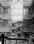 HABS interior photograph of the central court of the Bradbury Building, emphasizing the ornamental ironwork on the stairways and open walkways and the large skylight.
