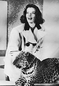 Katharine Hepburn, smiling, and leopard looking off-camera