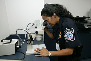 Fake passport - U.S. CBP Office of Field Operations agent checking the authenticity of a travel document at an international airport using a stereo microscope