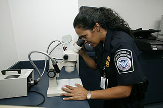 Counterfeit - U.S. CBP Office of Field Operations agent checking the authenticity of a travel document at an international airport using a stereo microscope