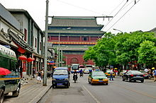 A view up a well-trafficked street to a large dark red building with a Chinese-style roof. On either side are rows of shops. In the foreground is a large metal gantry holding up wires for a trolleybus in the background