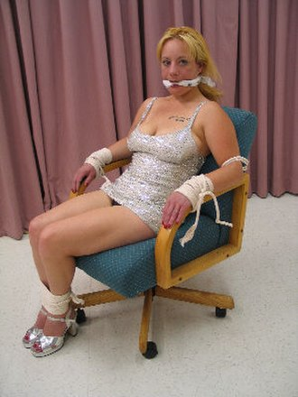 Interrogation scene - A woman is tied to a chair, and gagged.