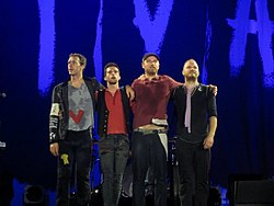 Coldplay members standing side-by-side onstage wearing costumes inspired by French revolutionaries